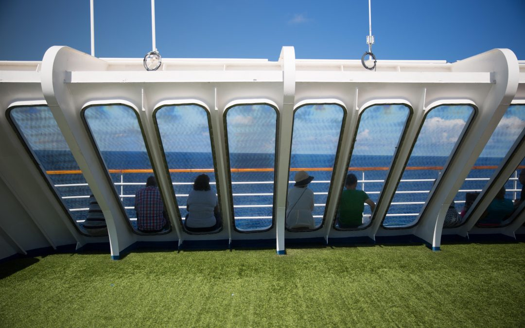 Passengers scan the ocean from the deck of a cruise ship. Behind them is a golf course. Many cruise ships today promise endless entertainment through a myriad shipboard activities like golf, spas, swimming pools, gyms, yoga and others. Almudena Toral/Univision.