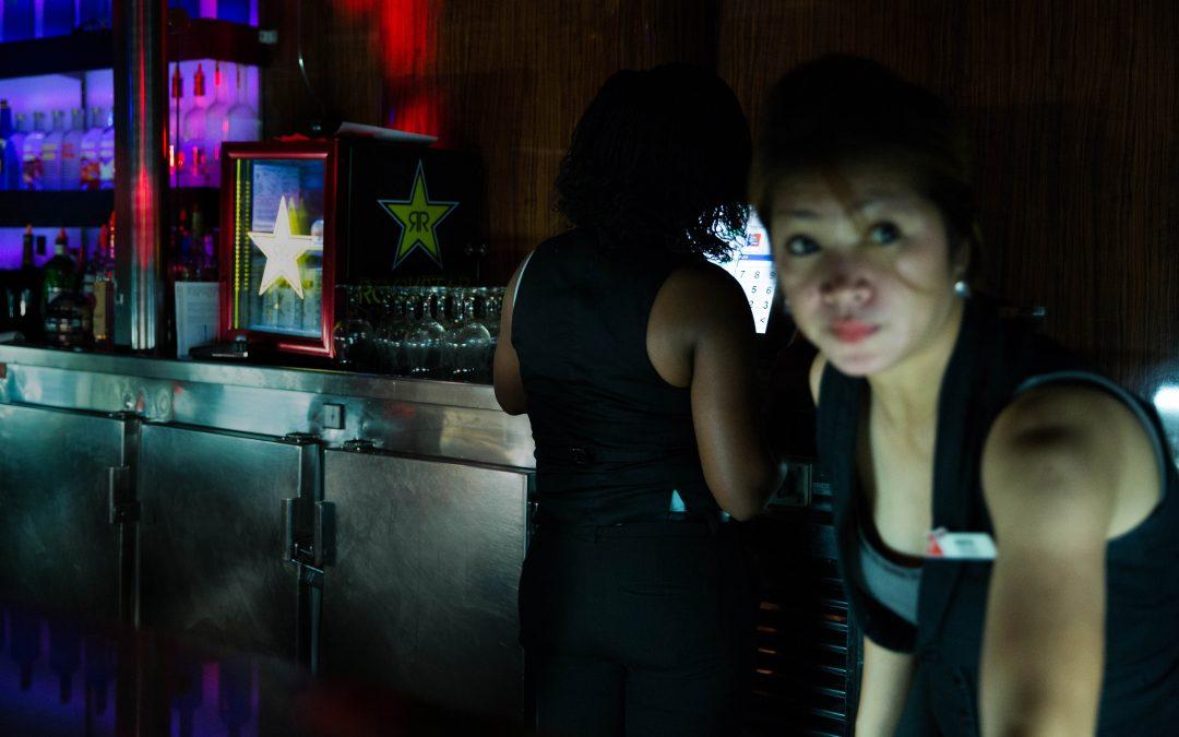 Dos trabajadoras sirven tragos en uno de los clubs nocturnos de un barco de Carnival la noche de Halloween. La venta de alcohol es una de las principales fuentes de ingresos a bordo. Almudena Toral/Univision