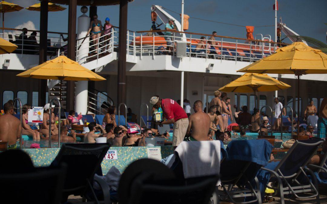 Un trabajador de cubierta (centro, de rojo) recoge bebidas en la piscina de un crucero. Los pasajeros no se preocupan por pagar en efectivo, ya que las compras a bordo se efectúan con una tarjeta magnética vinculada a las cuentas bancarias del turista. Almudena Toral/Univision