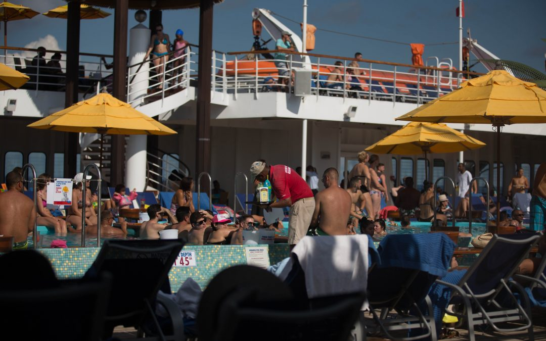 A deck hand (center, in red) picks up drinks at a cruise ship swimming pool. The passengers don't need to worry about cash, as purchases on board are made with magnetic strip cards linked to guest accounts. Almudena Toral/Univision