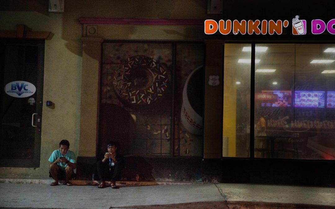 Dos jóvenes asiáticos fuman en una acera de Nassau, Bahamas, un sábado por la noche. Un Dunkin Donuts ya cerrado les da conexión wifi para su teléfono móvil, como otros lugares de comida rápida de la calle Bay. La mayoría no puede permitirse la conexión diaria a internet desde el barco ya que les cuesta lo mismo que a los turistas. Almudena Toral/Univision