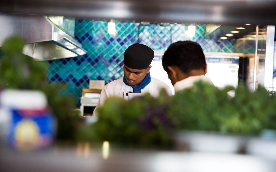Un par de trabajadores indios cortan vegetales durante un almuerzo en una estación de sándwiches. La nacionalidad india es una de las más presentes en las cocinas. Algunos de ellos explican que la industria encuentra en el país asiático profesionales con buena formación para estar entre fogones. Almudena Toral/Univision