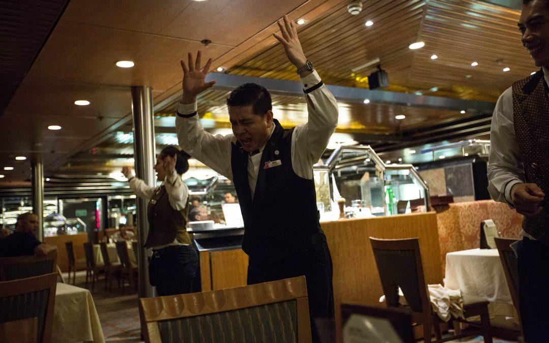 Un supervisor de un restaurante baila al final de una cena. Los cruceros utilizan las canciones pegadizas y repetitivas como hilo conductor durante el viaje. A los empleados se les motiva para que se mantengan siempre positivos y sonrientes. Almudena Toral/Univision