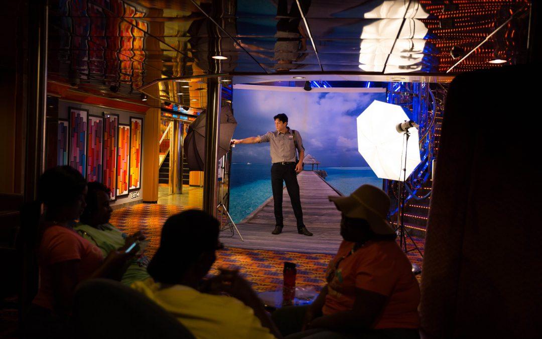 Un fotógrafo prepara las luces para una sesión de retratos al lado de una escalera. Se toman, revelan e imprimen miles de fotografías a bordo, con el riesgo de no ser vendidas y quedarse olvidadas en los pasillos que las exhiben. Almudena Toral/Univision