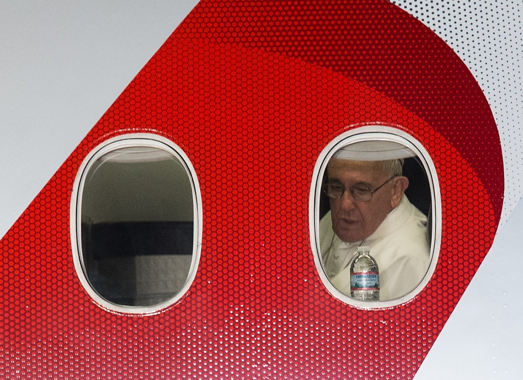 Pope Francis looks out the window of his plane before departing Philadelphia on September 27, 2015 at the end of his six-day visit to the US. AFP PHOTO / NICHOLAS KAMM (Photo credit should read NICHOLAS KAMM/AFP/Getty Images)